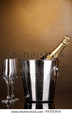 Bottle of champagne in bucket and goblets on brown background
