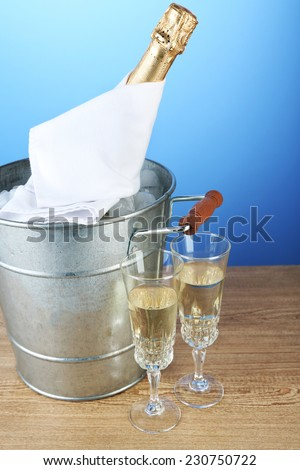 Bottle of champagne in metal ice bucket and two glasses on wooden table on color background