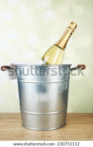 Bottle of champagne in metal ice bucket on wooden table on light background