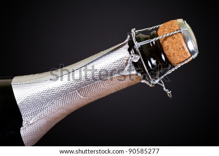 Bottle of champagne with cork over black background