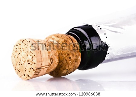 Bottle of champagne with cork over white background