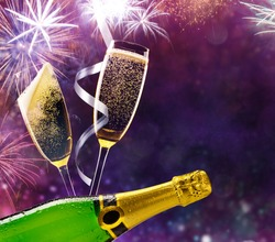 Bottle of champagne with glasses over fireworks background. Celebration concept, free space for text