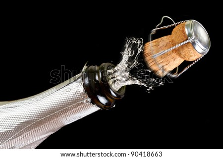 Bottle of champagne with splashes over black background