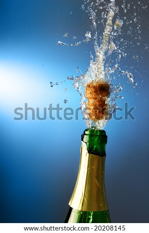 Bottle of champagne with splashes over blue background