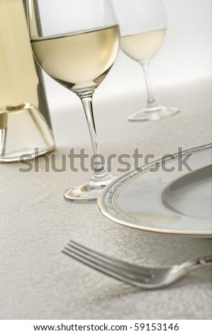 bottle of chardonnay wine and two glasses, focus is on front glass, plate and fork in the foreground on ornate table cloth