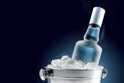 Bottle of cold vodka in bucket of ice on dark background