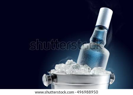 Bottle of cold vodka in bucket of ice on dark background Zdjęcia stock ©