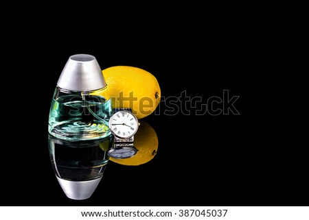 Bottle of Cologne with wrist watch and lemon are lying on the polished black surface #387045037