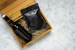 Bottle of craft beer and packaging of snacks in a wooden gift box on grey concrete background with copy space.