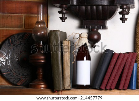 Bottle of craft beer with blank label template standing on a shelf with books under an old clock