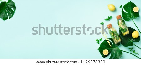 Bottle of detox water with mint, lemon and tropical monstera leaves on blue background. Flat lay. Banner. Citrus lemonade. Summer fruit infused water. Top view with copy space