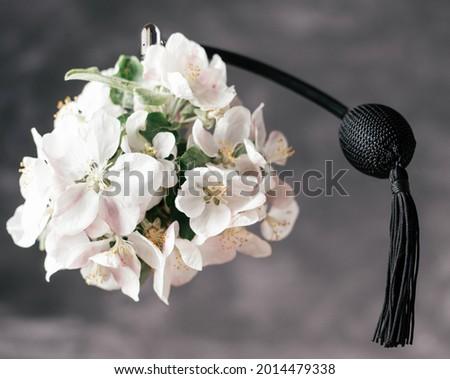 Bottle of eau de toilette or perfume made from apple blossom with long black tassel spray pomp soars in air on dark gray background Stock fotó ©