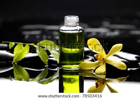 bottle of essential oil and green leaf with orchid reflection