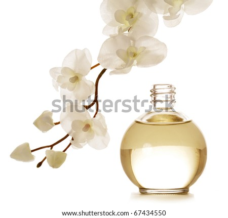 bottle of essential oil and orchid flowers