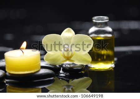bottle of essential oil and yellow orchid with candle on pebble