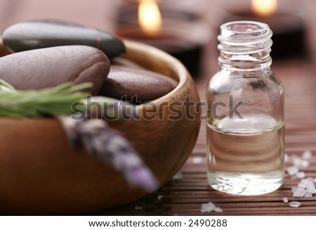 bottle of essential oil, massage stones,candles,lavender and bath-salt in a tight composition