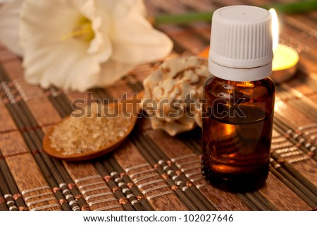 Bottle of essential oil, sea salt in the wooden spoon, burning candle and narcissus