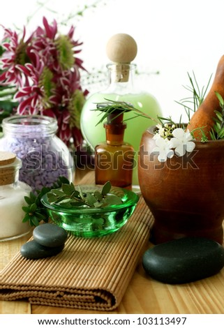 Bottle of essential oil, stones,  mortar and flowers
