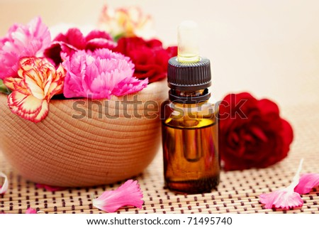 bottle of flower essential oil with fresh carnation flowers  - beauty treatment