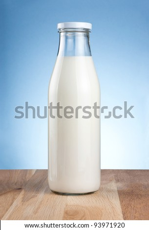 Bottle of fresh milk is wooden table on a blue background