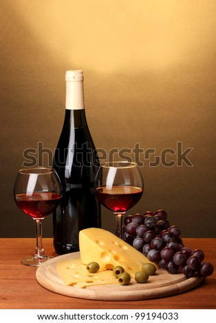 Bottle of great wine with wineglasses and cheese on wooden table on brown background