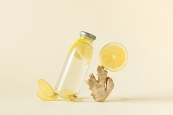 Bottle of infused water with ginger and lemon over light yellow background. Balanced still life of detox water and ingredients.