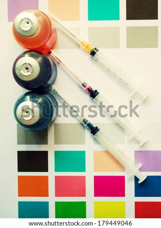 Bottle of ink printer has three colors. Colors is red, yellow and blue with syringe on colored paper.