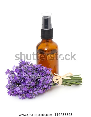 bottle of lavender oil and bunch of lavender flowers