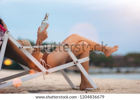 bottle of liquid light beer in hand of young woman, feel comfortable and relax sitting on deck chair beach, happy enjoy with  drink alone