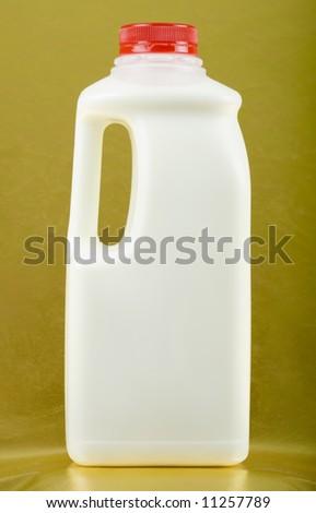 Bottle of milk on golden background; close up