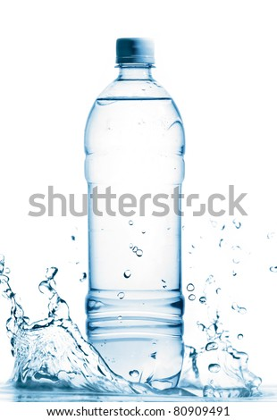 bottle of mineral water is standing in splashing water cut out from white