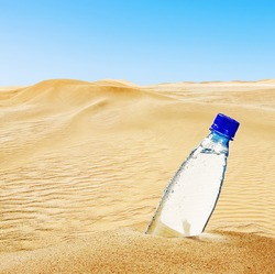 bottle of mineral water on the sand in the desert