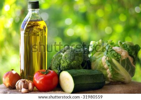 Bottle of olive oil and vegetables.