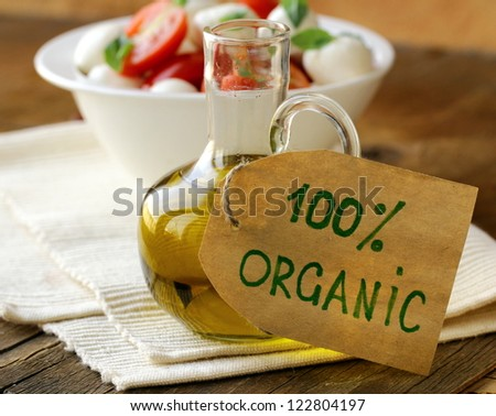 bottle of olive oil on a wooden table - stock photo
