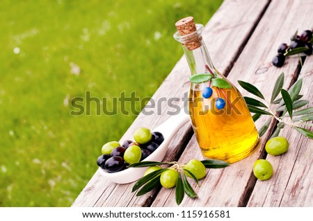 Bottle of olive oil with fresh black and green olives