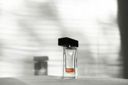 Bottle of perfume, close up. Leftover of scent. Shadows and light playing. Beauty concept. Luxury product. Perfume testing.