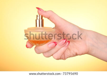 bottle of perfume in the hand  on yellow background