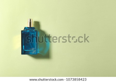 Bottle of perfume on color background, top view #1073858423