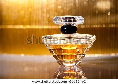 Bottle of perfume with reflection on gold