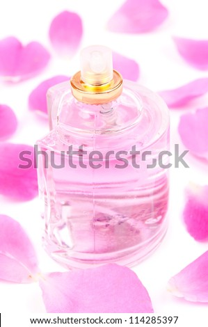 Bottle of pink perfume and pink rose petals around, on the white background