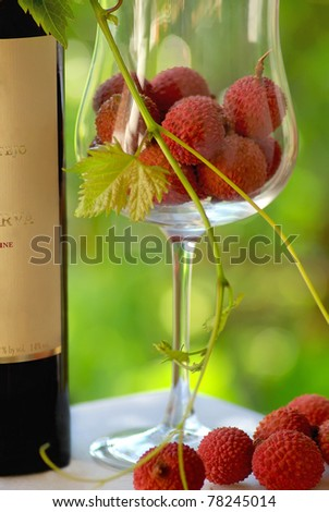 Bottle of Red wine and red fruits in glass.