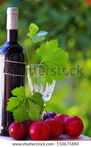 Bottle of red wine and ripe fruits