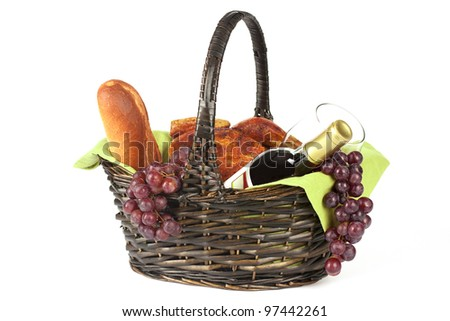 bottle of red wine glass grapes bread and chicken in picnic basket on white background