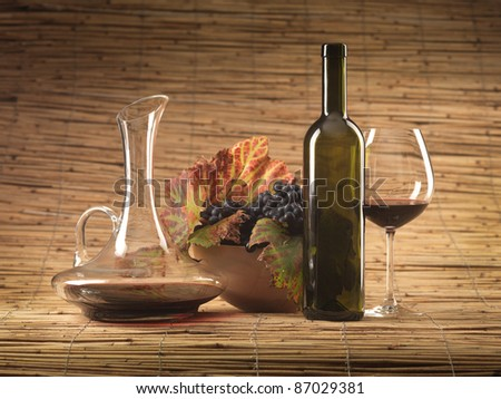 bottle of red wine, glass, pitcher and grapes on wicker background