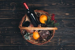 Bottle of red wine in Christmas gift basket.