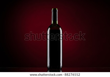 Bottle of red wine on red gradient background
