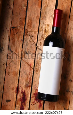 Bottle of red wine with a blank label in a used wooden crate with grape juice marks