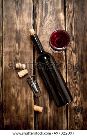 Bottle of red wine with a corkscrew and corks. On a wooden table.