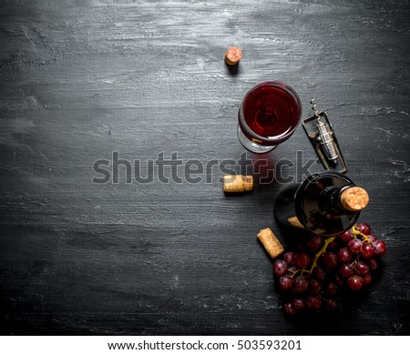 Bottle of red wine with a corkscrew. On a black wooden background. #503593201