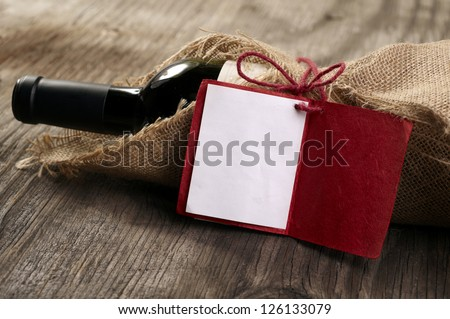 Bottle of red wine with a message on wooden table